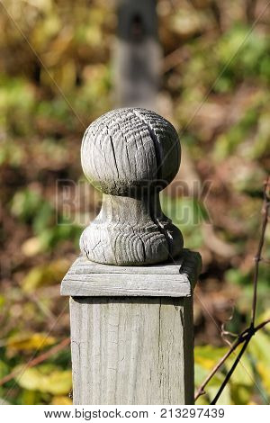 Old unpainted rounded top fence post bordering a garden.