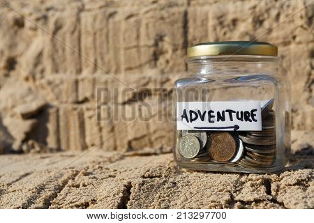 Glass jar with coins for adventure on rock background, copy space. Money box, distribution of cash savings concept.
