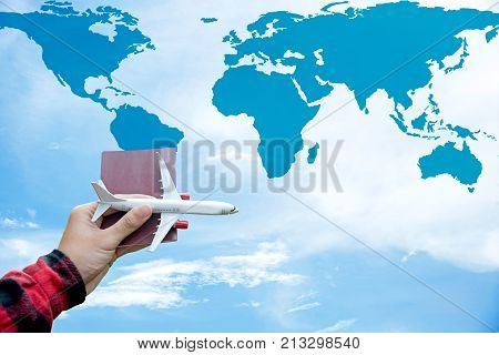 Tourist holding airplane and passport flight travel traveller fly on the blue sky and world map for travelling citizenship air on the around world. Travel Concept.