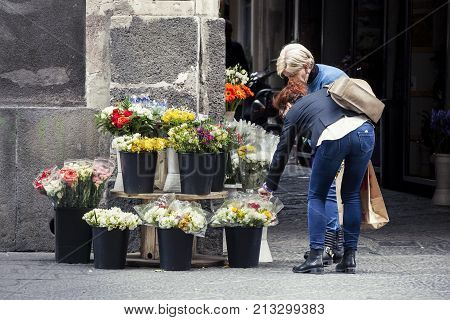 CATANIA, ITALY. April 03, 2015: Woman choosing and buying flowers from street vendor. Location: Catania (old town) Sicily, Italy.