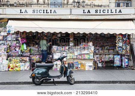 CATANIA, ITALY. April 03, 2015: The historic center of Catania, Sicily. Italy. Newsstand on the square (Piazza Stesicoro). A scooter is parked in front of the newsstand and some pedestrians walking.
