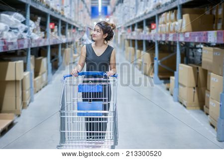 Young asian woman shopping with shopping cart for choosing furniture at department store or warehouse furniture store with happiness.
