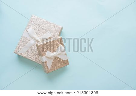 Present with red bow on pink background with tittle sparkles. Flat lay trendy style.