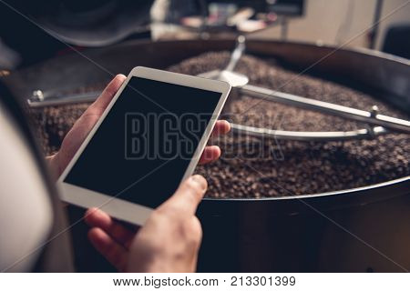 Close up male hand keeping tablet while having job at factory. He situating near technical equipment with coffee grains. Job concept