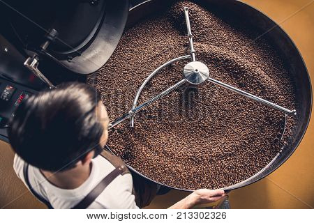 Top view coffee roaster worker controlling beans falling into spinning cooler professional machine. Arabica concept