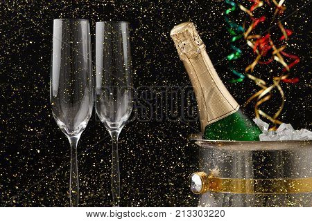 Celebrating new year, birthday, xmas party. Bottle of champagne in a bucket, flutes and colorful tinsel on black backgroud with golden glitters, copy space. Mockup for postcard
