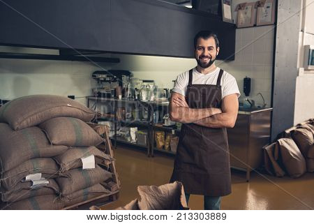 Cheerful bearded man standing near big bags with coffee corns in them. Occupation concept