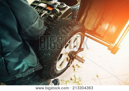 Car mechanic balancing car wheel on computer machine balancer in auto repair service, top view, sunlight effect