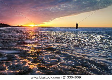 Walking On The Edge. Silhouette of a single man walking on the edge of the open water of a frozen lake on the coast of Lake Huron in Michigan.
