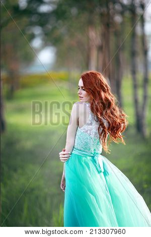 beautiful young girl with red hair in a lavish dress walking in the nature near trees