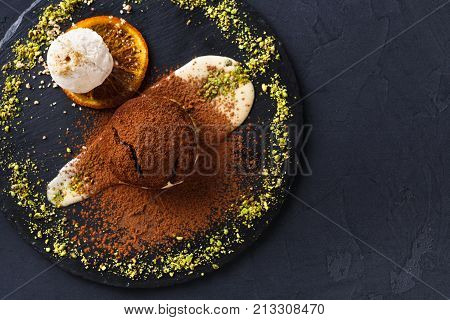 Exquisite dessert on black background. Chocolate fondant, creme anglaise and vanilla ice cream, sprinkled with cocoa on slate decorated with orange citron and pistachio crumble, top view, copy space