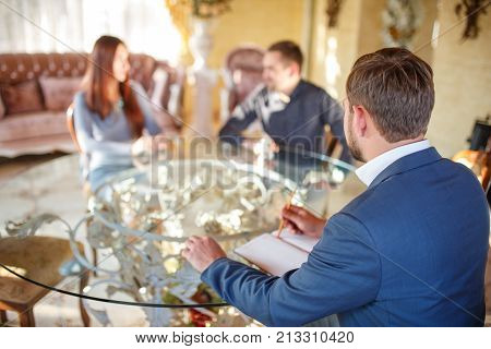 At the psychologist. Young couple sitting at the table, swearing, blurred background, the doctor is sitting in the chair, taking notes.