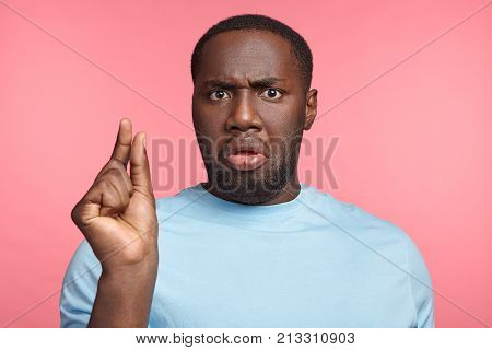 It Is So Tiny. Portrait Of Dark Skinned Man With Afro Hairstyle Dressed Casually, Gesticulates With