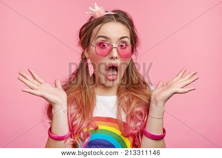 Horizontal Portrait Of Horrified Fashionable Woman Gestures In Puzzlement, Being Shocked And Surpris