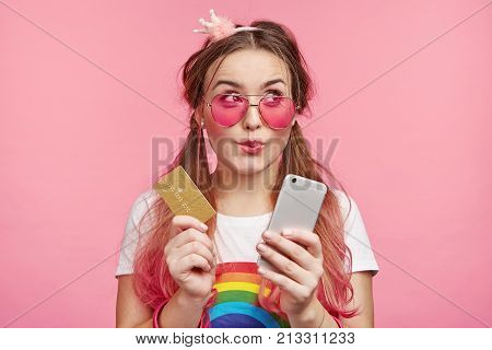 Horizontal Portrait Of Female Chick Has Dreamful Expression, Imagines New Clothes, Going Do Online S