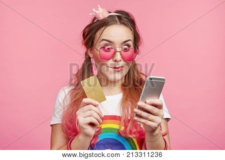 Pleased Shocked Stylish Female In Pink Sunglasses, Rejoices Upcoming Shopping In Her Favourite Onlin