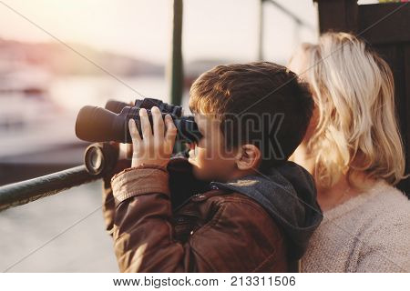 Little caucasian boy watching gazing looking searching for by binoculars with mother in sunset