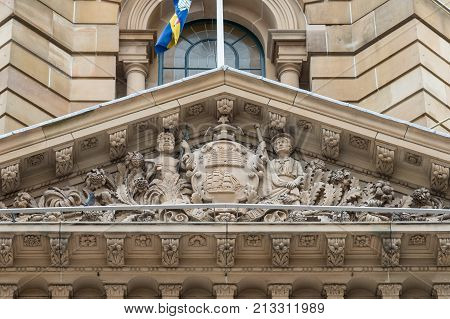 Sydney Australia - March 25 2017: Closeup of top of brown stone Town Hall focus on frieze with statues in front facade above entrance.