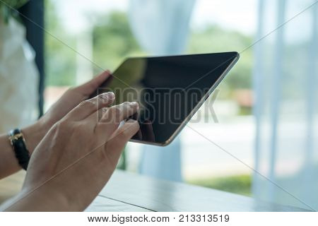 Closeup image of a woman holding and using smart phone in modern cafe with green nature outdoor background