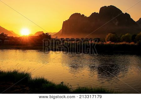 Sunset Over Nam Song River With Silhouetted Rock Formations In Vang Vieng, Laos