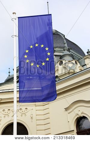 vertical flag of the European Union against the backdrop of a beautiful castle