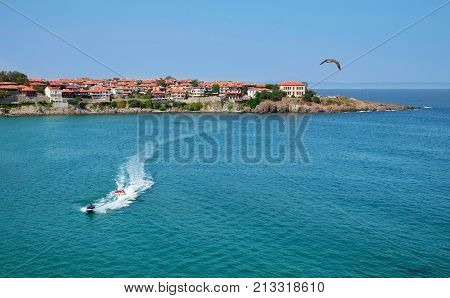 Landscape with the view of the part of old Sozopol town surrounded by the sea. There is an jet ski and vacationers in the sea. Bulgaria the Black Sea coast.