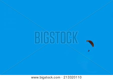 Passionate about Aeronautics people. Daring paraglider flying high in the blue sky. Air sport and recreation. A powered glider with a dorsal power plant, providing the rise and moving in the air.