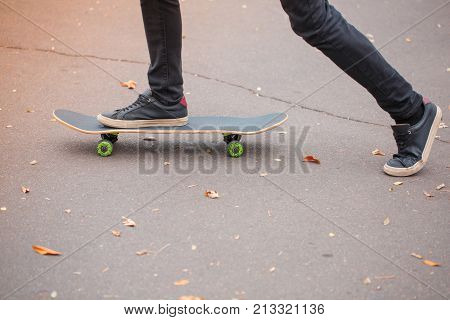 Close-up of a skateboarder's foot in black krosovkah on a skateboard, among the autumn leaves, a skateboarder rides a skateboard. The concept of sport.