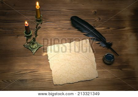 Blank letter page with copy space. Writer desk table. Blank crumpled paper page black feather pencandle and inkwell on table background. Education background.