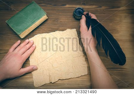 Man signing agreement or contract with feather pen in his hand on blank crumpled paper page with copy space. Person is wetting a pen in an inkwell and writes a letter. Writer desk table.