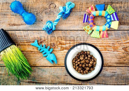 Toys for cat near dry food and grass in pot on wooden background top view.