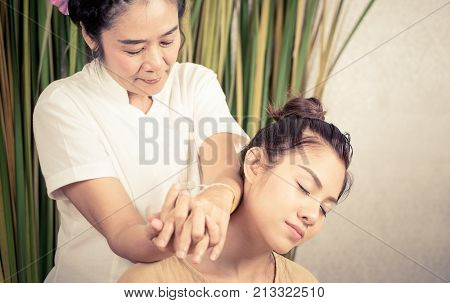Thai Therapist is massaging a woman on shoulder and neck