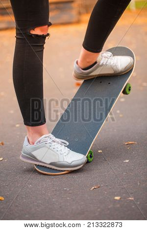 Close-up of a skateboarder's foot in black krosovkah on a skateboard, among the autumn leaves, a skateboarder performs a trick on a skateboard. The concept of sport.