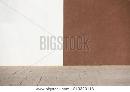 City street background. White and brown plastered wall and sidewalk pavement