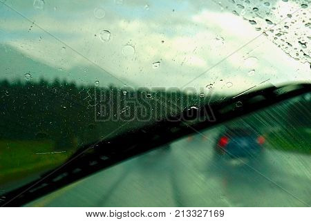 bad rainy weather as viewed through the front window of a car and it's wipers