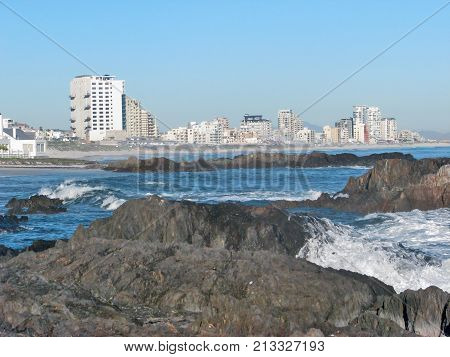 SEASCAPE, WITH HUGE BOULDERS IN THE FORE GROUND AND HIGH RISE BUILDINGS IN THE BACK GROUND 0111