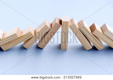 Strength And Leadership Business Concept - One Wood Toy Block Stop Domino Effect