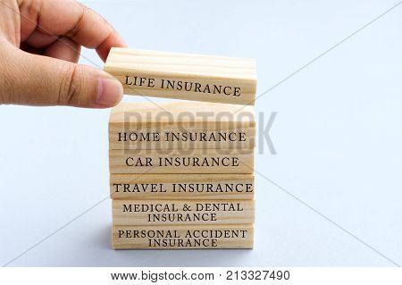 Hand Picking Wood Block with Word Life Insurance. Business Concept Type of Insurances on Wood Top Block with Word: Life Home Car Travel Medical and Dental Personal Accident.