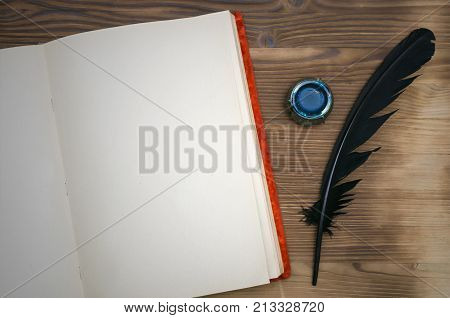 Open vintage book with blank paper page with copy space black feather pen and inkwell on table background. Education background. Writer desk table.