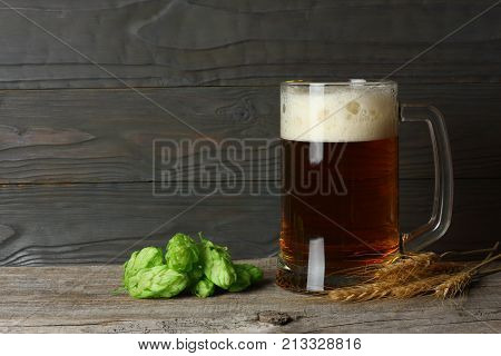 Glass Beer With Hop Cones And Wheat Ears On Dark Wooden Background With Copy Space. Beer Brewery Con