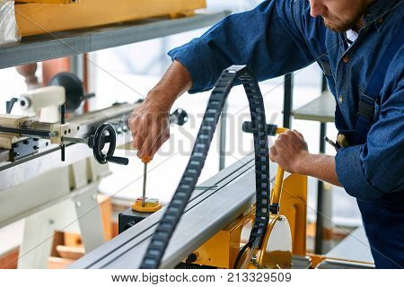 Closeup of workman  fixing machine unit tying screws with screwdriver at modern factory, copy space poster