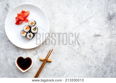Sushi roll with salmon and avocado on plate with soy sauce, chopstick, wasabi on grey stone background top view.