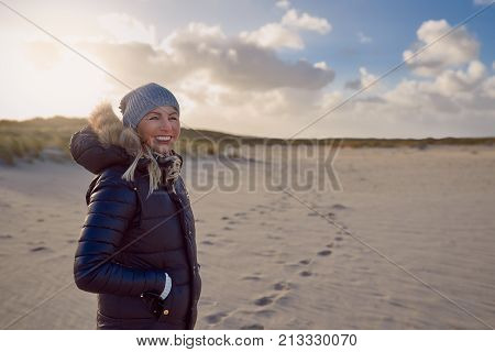 Trendy woman in a warm autumn outfit standing on a beach at sunset casting a long shadow across the sand looking to the side with a happy smile