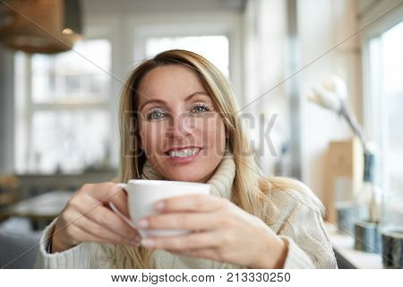 Portrait of a beautiful woman with long blond hair smiling and looking at camera while relaxing at home with a cup of coffee