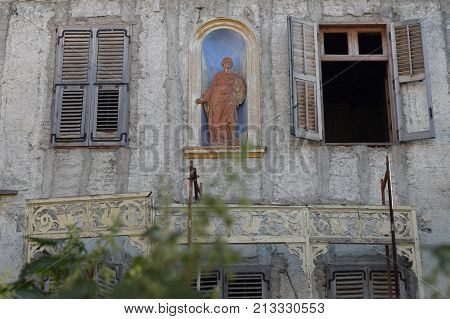 Decayed building facade with weathered statue in niche alcove arched recess. Neoclassical architecture Athens Greece.