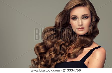 Brunette brown girl with long  and   shiny curly hair .  Beautiful  model woman  with curly hairstyle. Care and beauty of hair