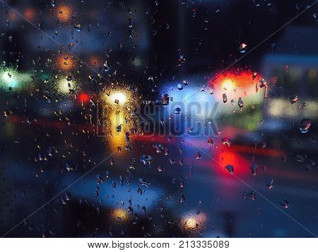 Drops of water during the rain in a city. Water covers the window glass, a blurred city lights are on the background. Lights of different colors.
