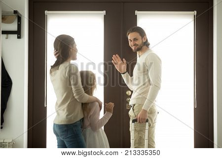 Mother and daughter seeing off father leaving for business trip, mom with kid girl saying goodbye to dad waving hand standing at home door holding travel case ready to go, family separation, good bye