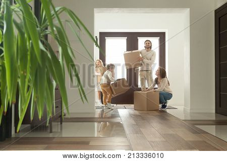 Happy family with kids holding boxes with belongings, excited couple and children standing in modern house hallway looking around moving in own bought rented real estate, welcome to new home concept