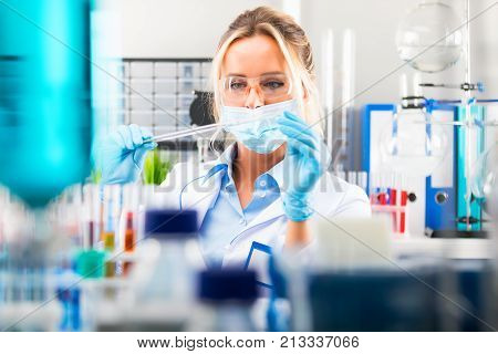 Young attractive female scientist in protective eyeglasses gloves and mask preparing laboratory equipment for tests